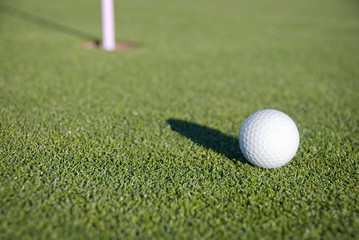 Golf Ball on the Green Near the Pin