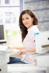 Young secretary working on computer in office