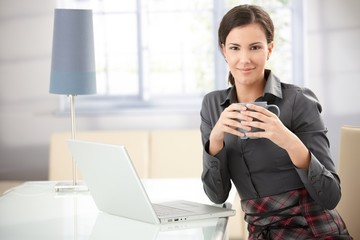 Pretty woman drinking tea at home using laptop