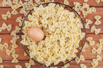 Uncooked raw pasta in glass plate with egg