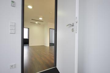 offene weiße Holztür mit Blick in den Flur