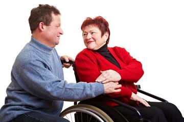 Ehemann unterstützt Frau im Rollstuhl