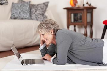 seniorin mit laptop im wohnzimmer