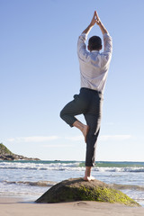 Geschäftsmann macht Balanceübung am Strand
