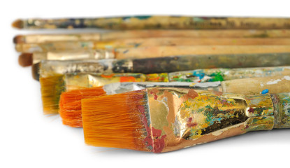 Isolated brushes. Collection of colorful brushes spotted with oil or acrylic paint in a row isolated on white background, selective focus