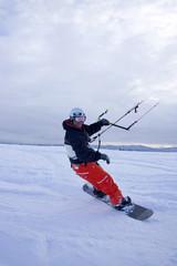 Snowkiting on snowboard.