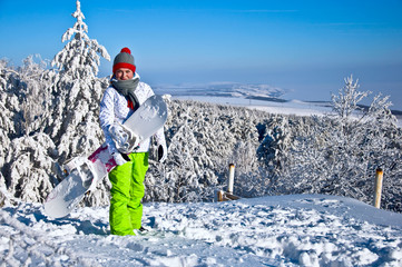 Beautiful woman with snowboard stands on mountain.