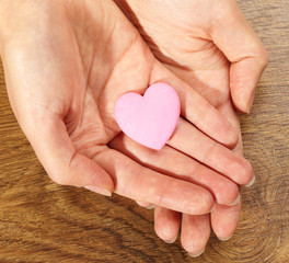 Woman holding pink heart in the hand