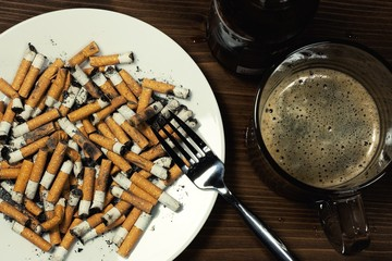 Plate with cigarettes stub with fork and beer