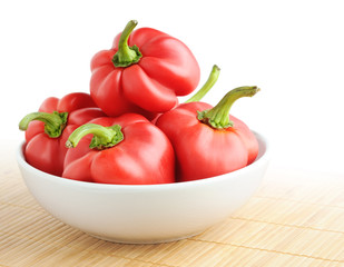 Red bell peppers in a bowl on a mat over white background