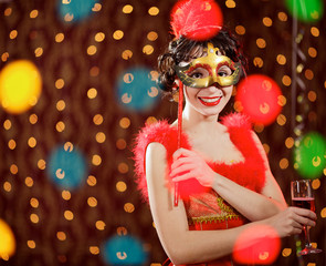 Lady in red dress at the carnival with champagne flute and mask