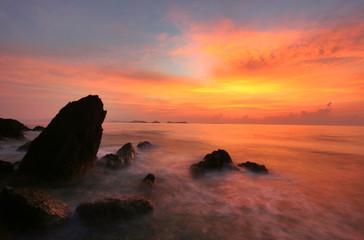 Tropical rock beach silhouette at sunrise