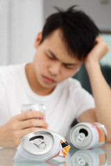 Drunk man with beer cans. Focus on crushed beer can.