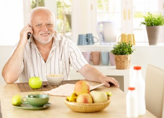 Healthy pensioner using cellphone at breakfast