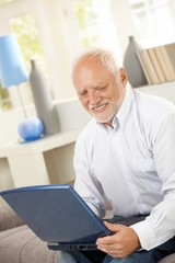 Smiling elderly man looking at computer screen