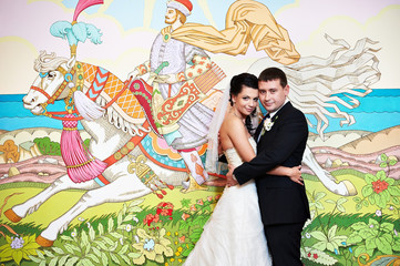 Happy bride and groom on background picture of fairy tales