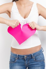 Angry female tearing paper heart apart