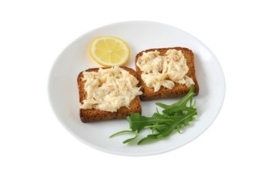 toasts with codfish and lemon on a plate