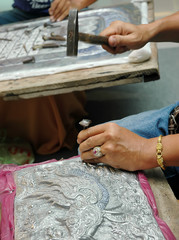 Craftsman carving a souvenir from Metal