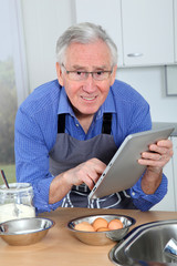 Elderly man looking at recipe on electronic tab
