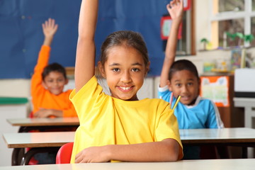 Primary school children signal with raised hands