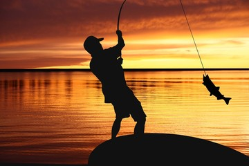 Foto op Canvas Vissen Fisherman with fishing tackle and catching fish at sunrise