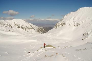Climber reaching the summit of the Retezat mountain, Romania