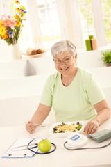 Healthy elderly woman eating salad