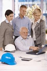 Senior architect showing work to team on laptop
