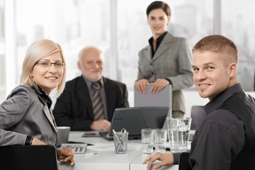 Mid-adult businesspeople sitting at meeting