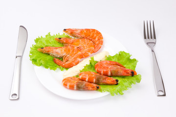 Royal shrimps on leaves of green salad in a white plate