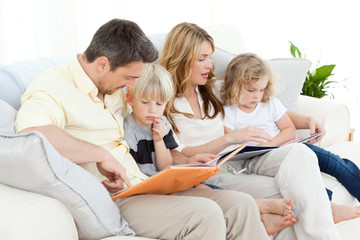 Family reading a book on their sofa