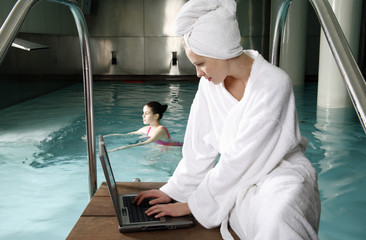 Woman on computer next  to a swimming pool