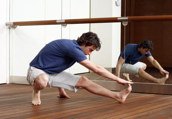 Young man stretching in gym