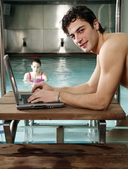 Man on computer next to a swimming pool