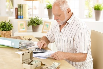 Senior man doing calculation at home