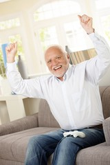 Senior happy winning computer game