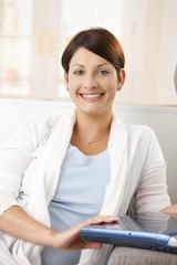 Portrait of happy woman holding laptop
