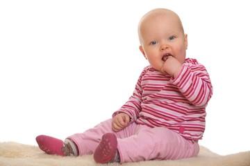 Glückliches Baby sitzt auf dem Boden