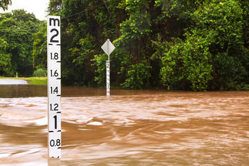 Flooded road with depth indicators in Queensland, Australia