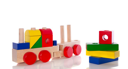 stacked wooden toy blocks and an educative wooden train isolated