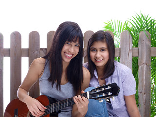 smiling teenagers playing guitar in the garden