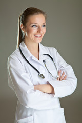 Medical doctor woman in uniform with stethoscope on neutral gray