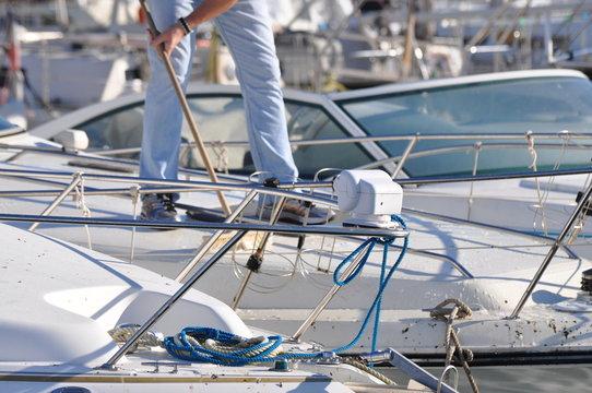 homme debout qui nettoie son bâteau au port