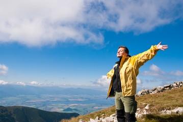 Woman enjoys sun in mountains on hiking
