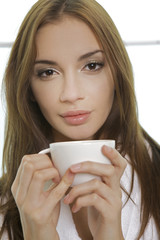 Portrait of cute teenage girl with cup of coffee