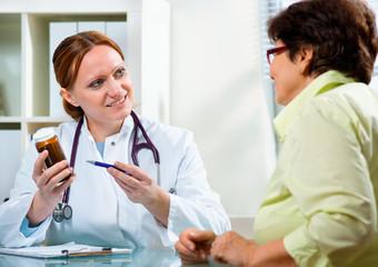 Doctor prescribes a medicine to a senior patient