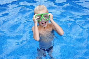 Little blondy boy having fun in the swimming pool
