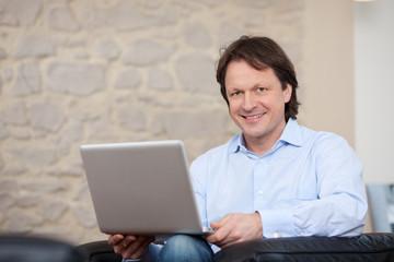 mann mit laptop sitzt im wohnzimmer