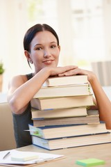 Smiling university student with pile of books